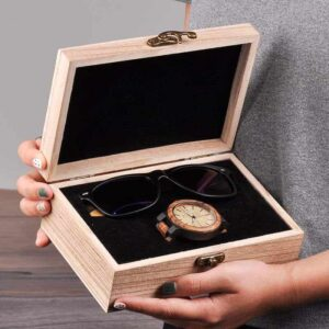 A lady opened a gift box with wooden glasses and a wooden watch